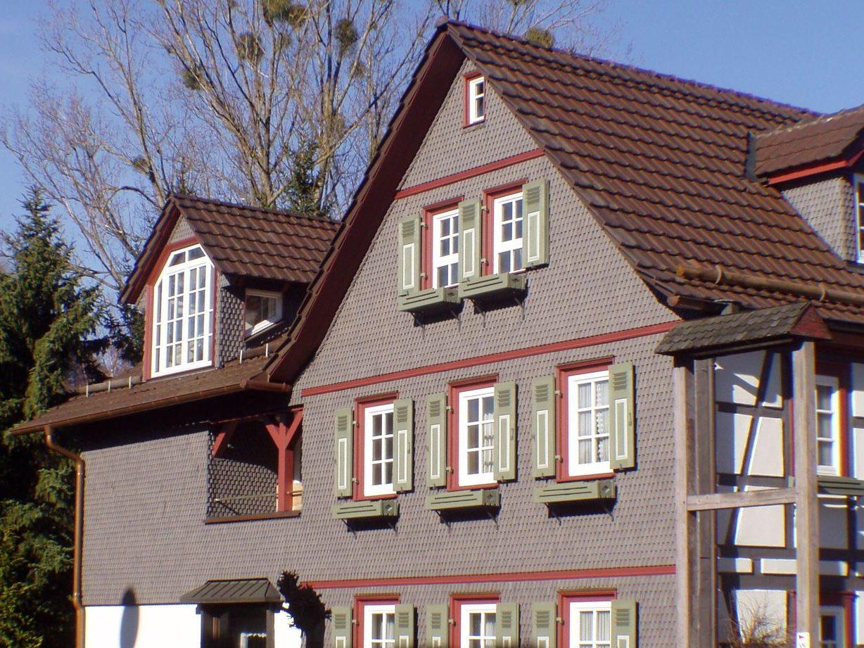 Wohnhaus mit Holzschindeln in grau-rot